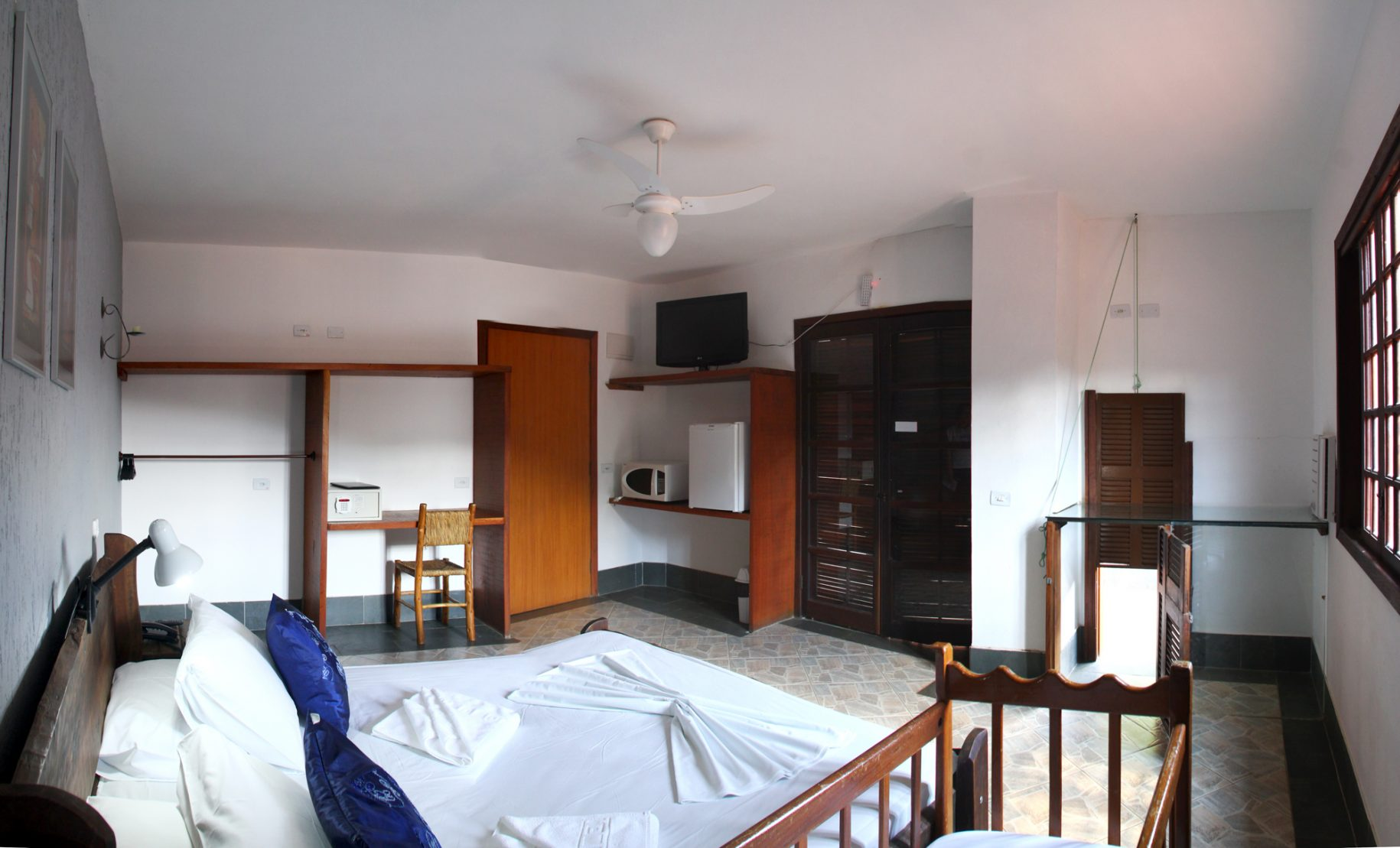 Quarto do hotel fazenda parque dos sonhos com berço, cama de casal, canil acoplado, tv de led, frigobar, microondas, cofre, ventilador de teto