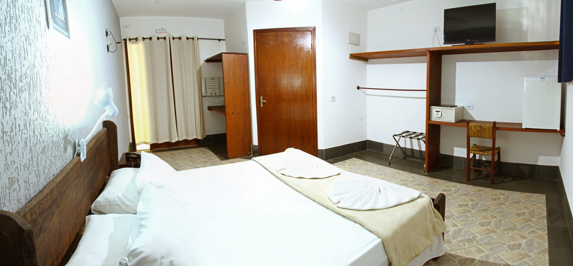 Quarto do hotel fazenda parque dos sonhos com cama de casal, cofre, frigobar, tv de led, ar condicionado quente e frio