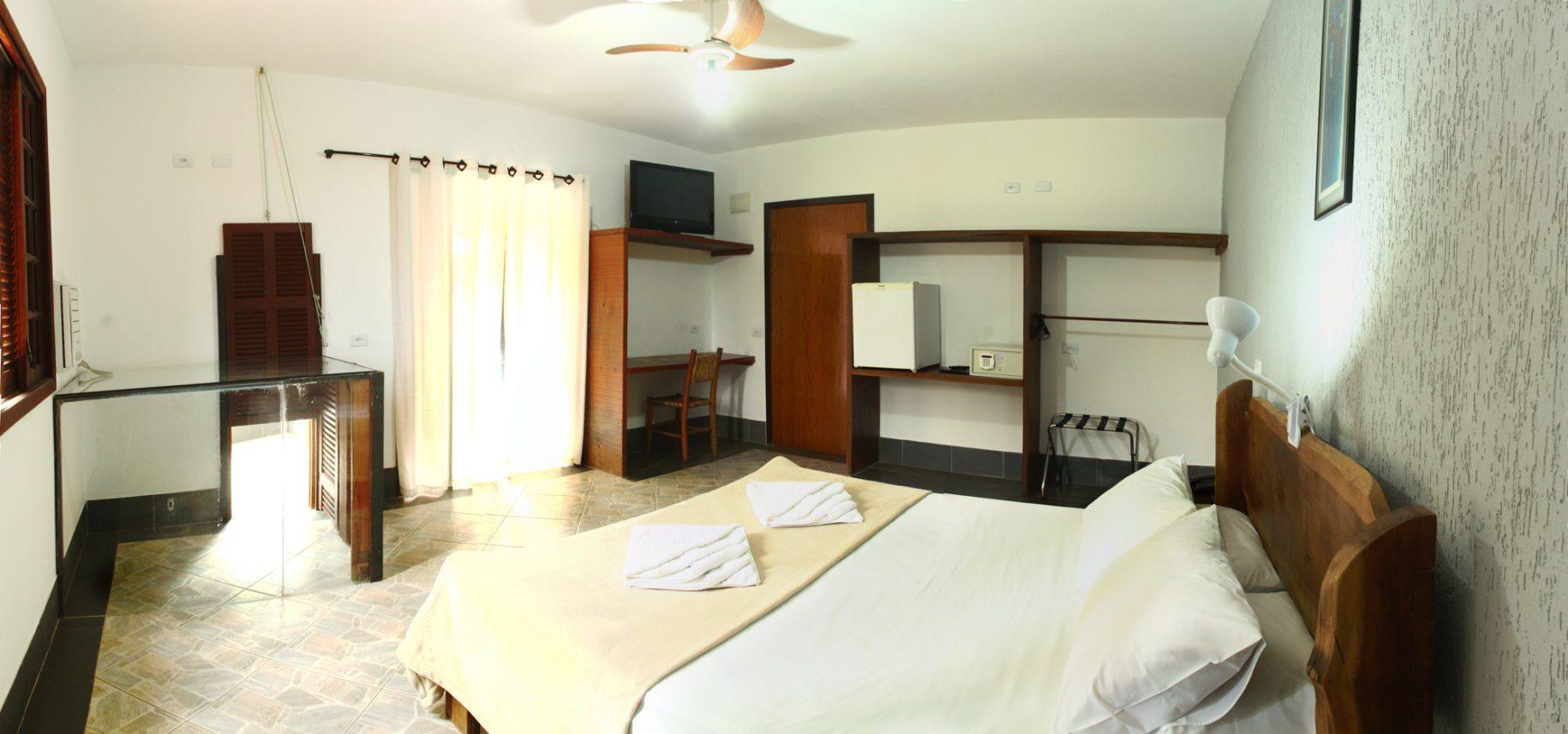 Quarto do hotel fazenda parque dos sonhos com cama de casal, cofre, frigobar, tv de led, ar condicionado quente e frio, canil acoplado