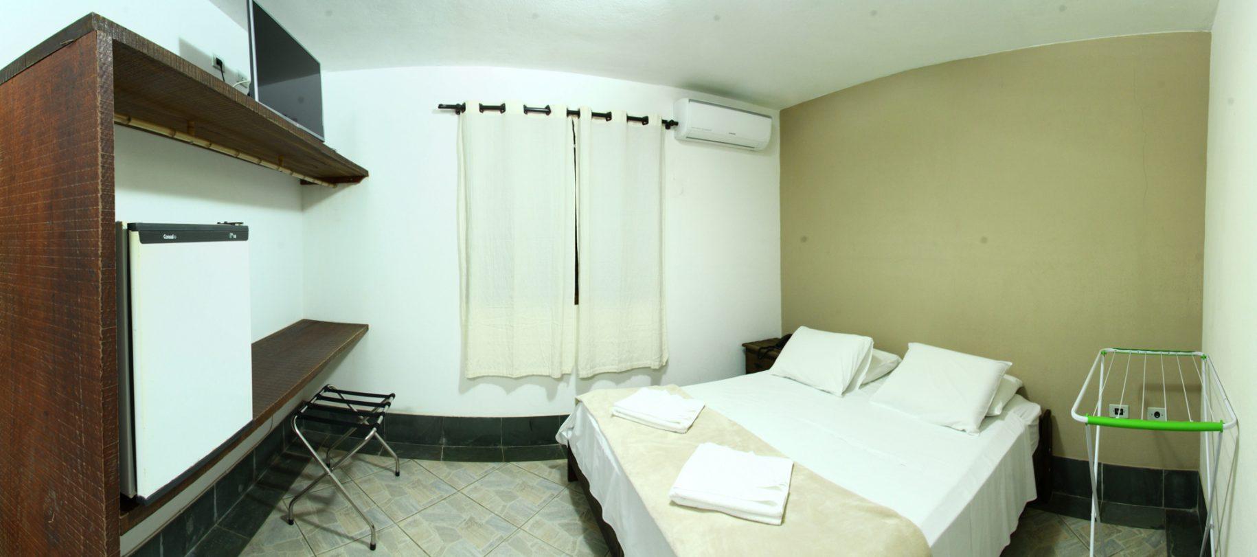 Quarto de um dos chalés do hotel fazenda parque dos sonhos com televisão de led, cama de casal, frigobar