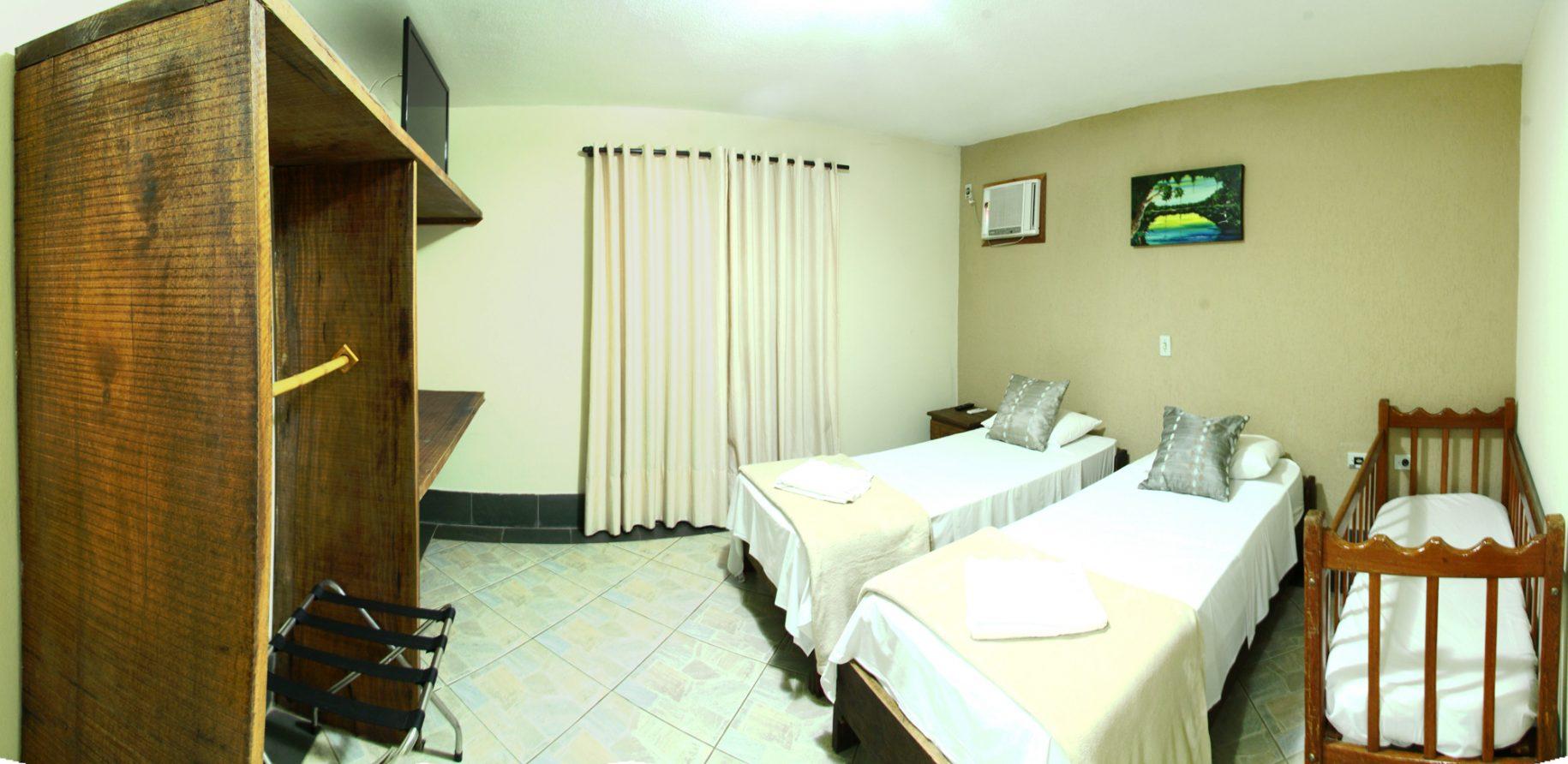 Quarto de uma das acomodações do hotel fazenda parque dos sonhos com, duas camas de solteiro, um berço, ar condicionado quente e frio, tv de led, cofre, frigobar