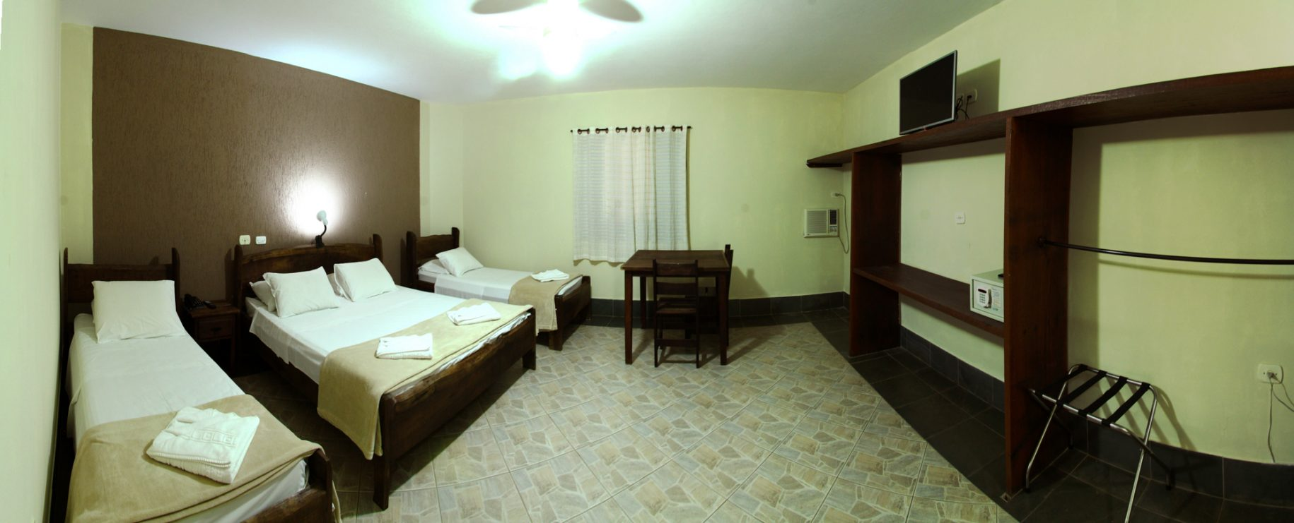 Quarto do chalé no hotel fazenda parque dos sonhos com cama de casal, duas camas de solteiro, mesa com cadeiras, ar condicionado quente e frio, tv de led, cofre e frigobar