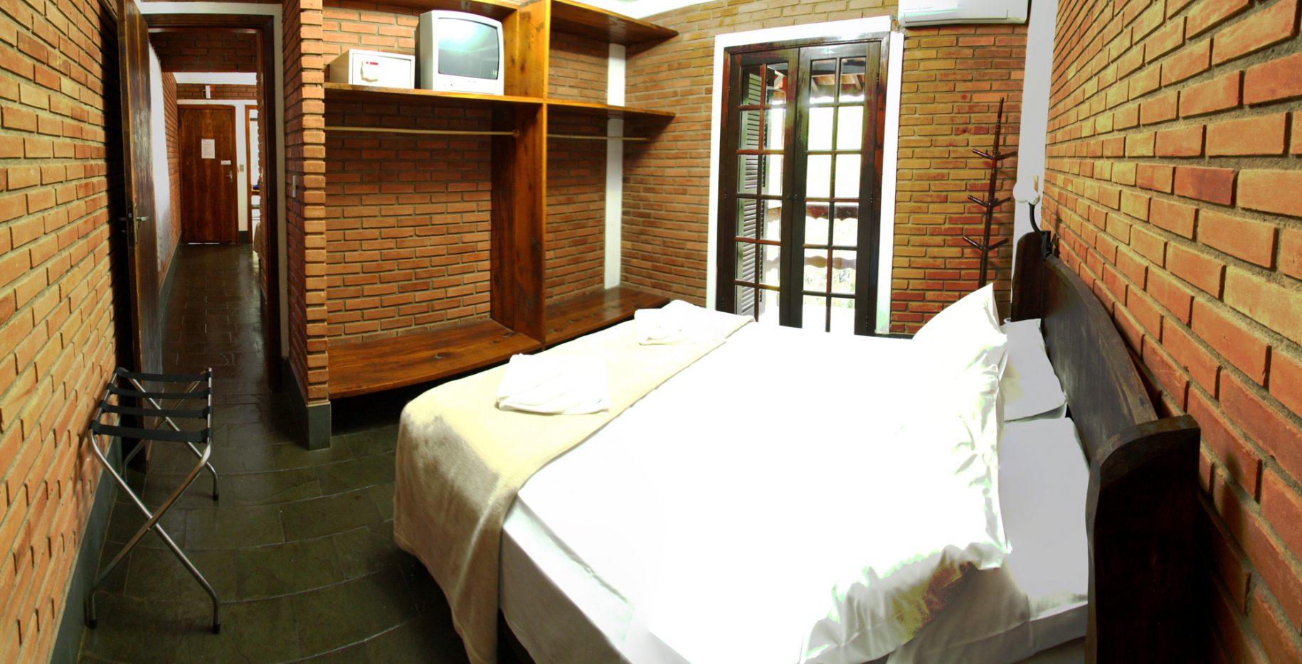 Quarto do chalé no hotel fazenda parque dos sonhos com cama de casal, televisão, cofre, ar condicionado quente e frio