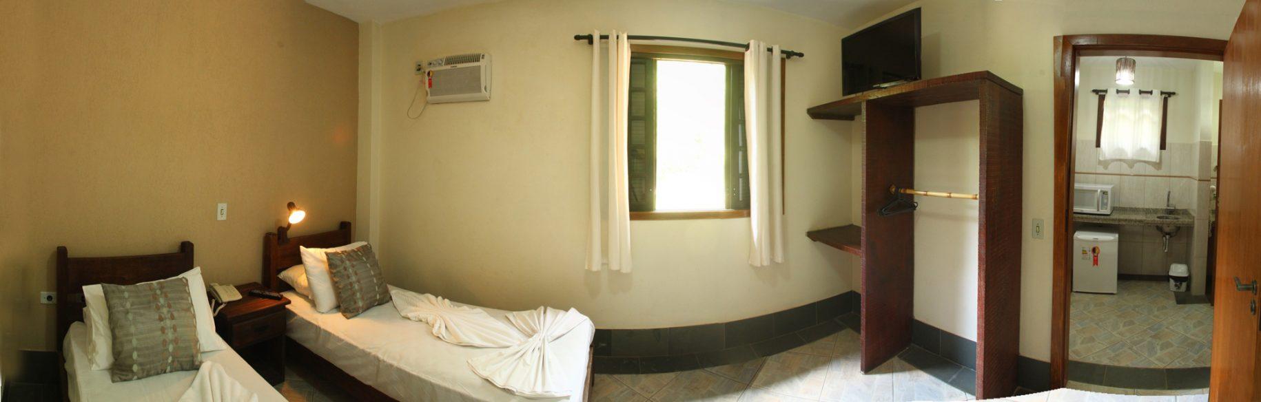 Foto com vista para o quarto de um dos chalés do hotel fazenda parque dos sonhos com, duas camas de solteiro, ar condicionado quente e frio, televisão de led, com vista também para copinha da mamãe com microondas, pia e frigobar