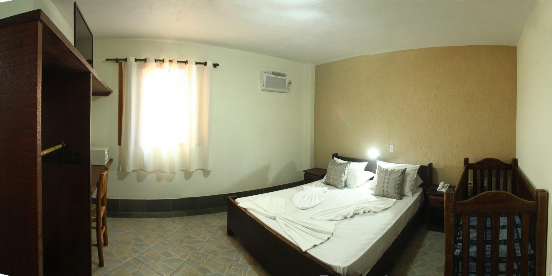 Quarto de um dos chalés do hotel fazenda parque dos sonhos com, cama de casal, berço, ar condicionado quente e frio, cofre, televisão de led e frigobar