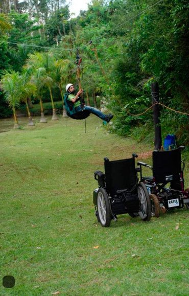 Usuário de cadeira de rodas descendo a tirolesa adaptada do hotel fazenda campo dos sonhos, ao lado duas cadeiras de rodas