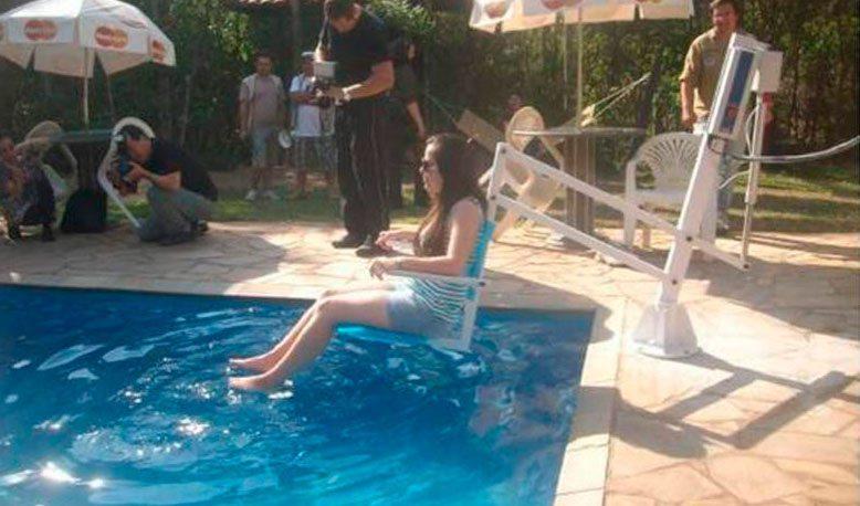 Mulher que é usuaria de cadeira de rodas, sendo colocada na piscina por uma cadeira motorizada