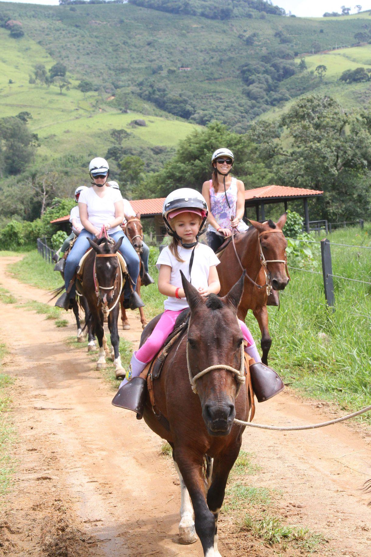 Uma criança pequena fazendo o passeio de ponei pelo hotel fazenda parque dos sonhos, e 4 adultos fazendo o passeio de cavalo