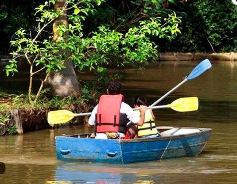 Pai e filho navegando pelo lago do hotel fazenda campo dos sonhos em um bote disponibilizado para a atividade pelo hotel
