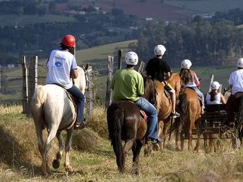 Adultos e crianças fazendo a cavalgada das montanhas do hotel fazenda campo dos sonhos e também o passeio de charrete