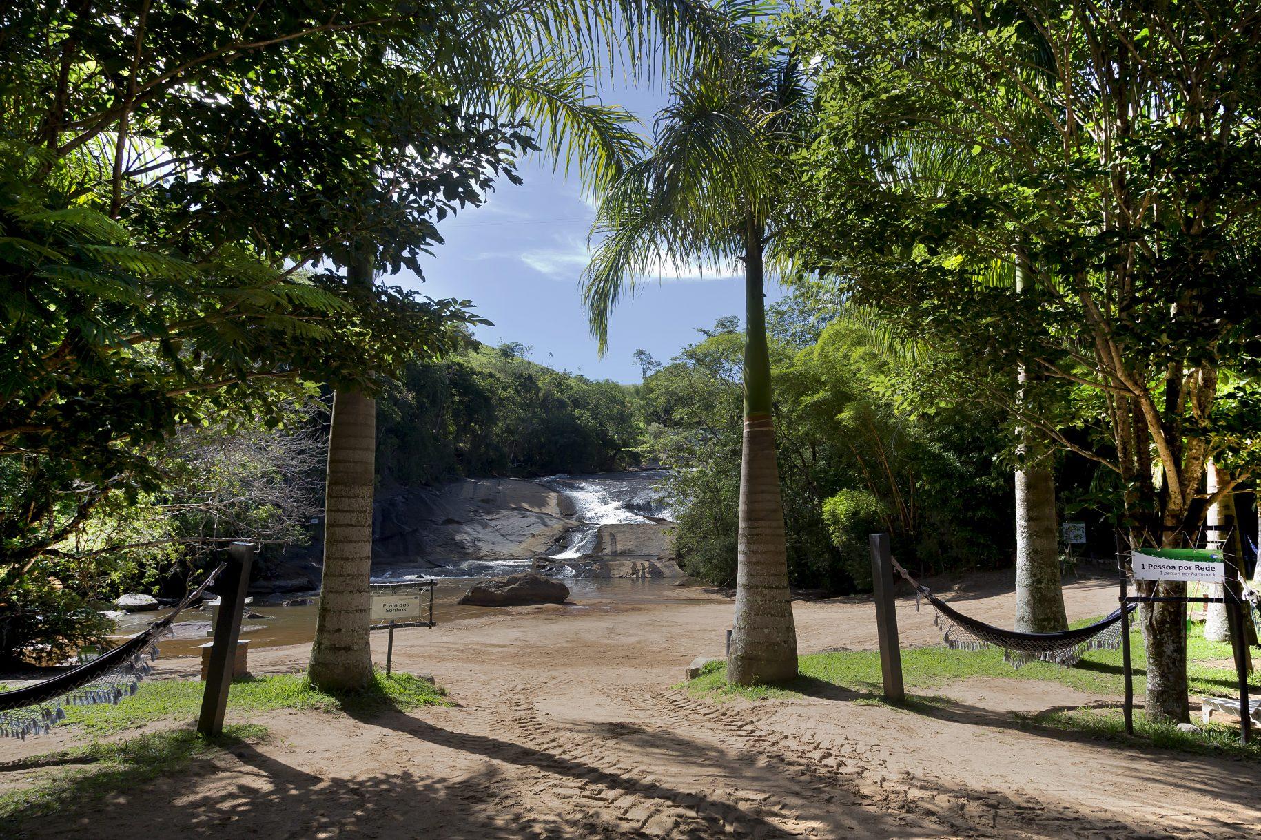 Imagem da prainha do hotel fazenda parque dos sonhos com redes para descanso em meio aos coqueiros
