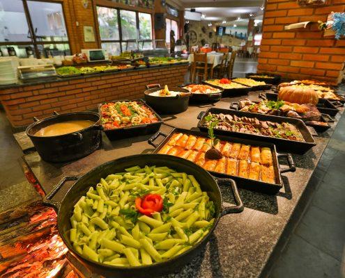 A foto mostra o fogão a lenha do hotel fazenda parque dos sonhos na hora do almoço, com a comida já servida sobre o fogão