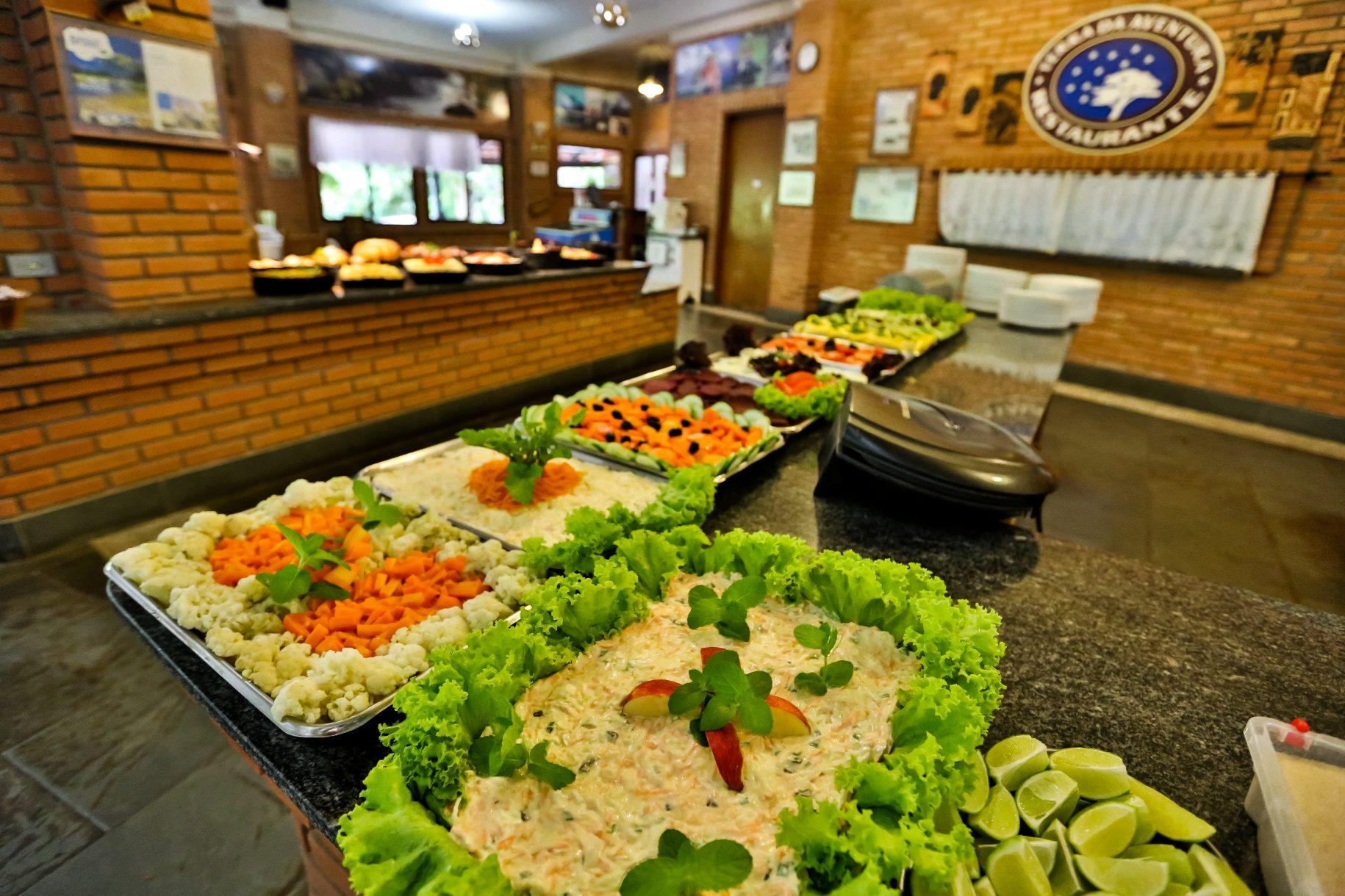 Foto do restaurante do hotel fazenda parque dos sonhos, com foco para as mesas de salada na hora do almoço