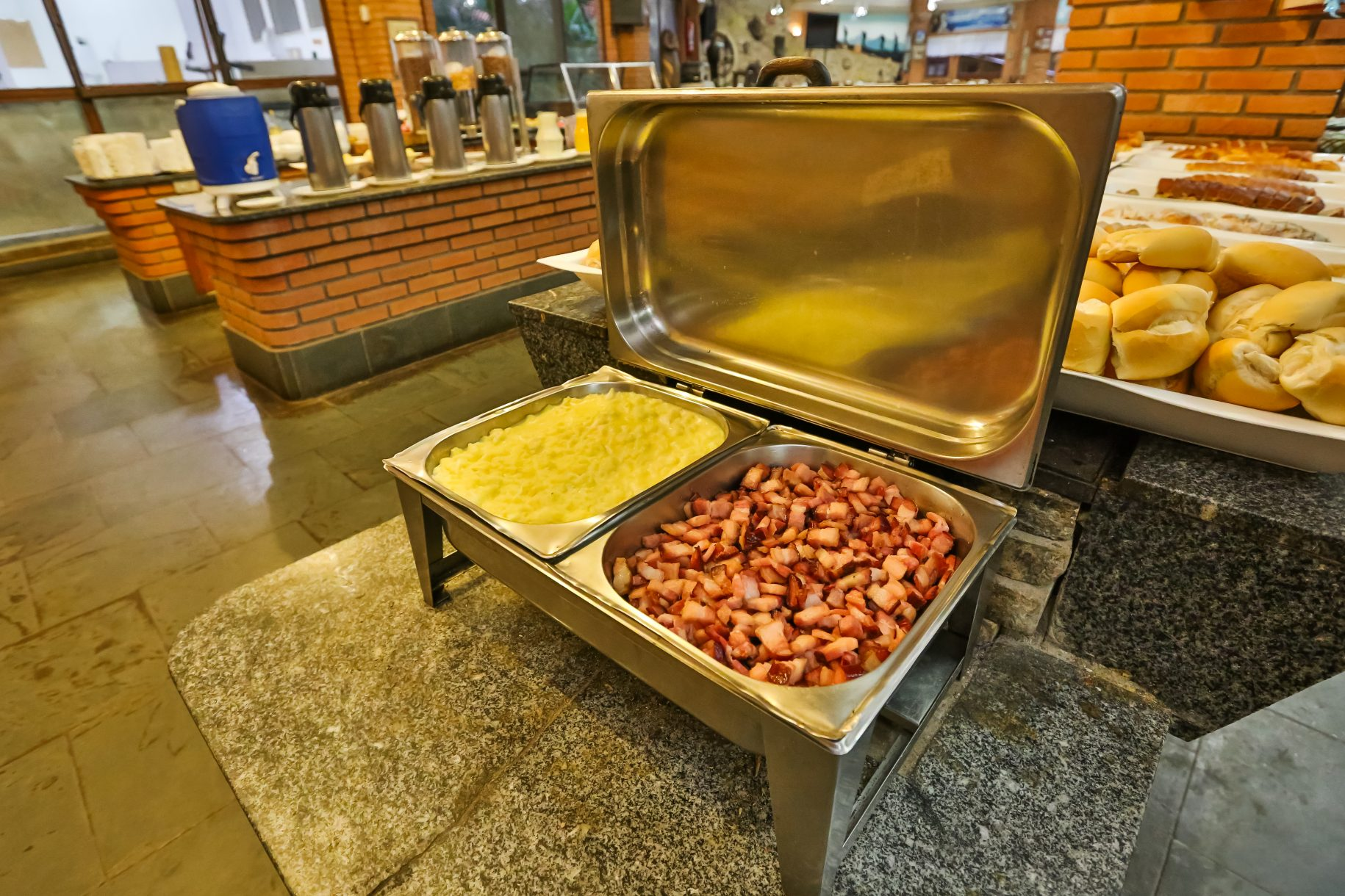 A foto mostra o café da manhã do Parque dos Sonhos com foco nos ovos mexidos com bacon