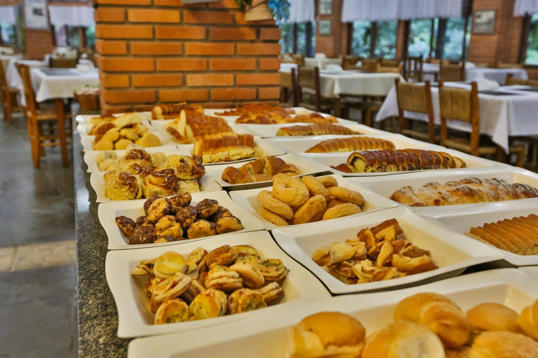 A foto mostra as inúmeras opções de comidas do café da manhã no hotel fazenda parque dos sonhos como carolinas de chocolate, pães caseiros etc.