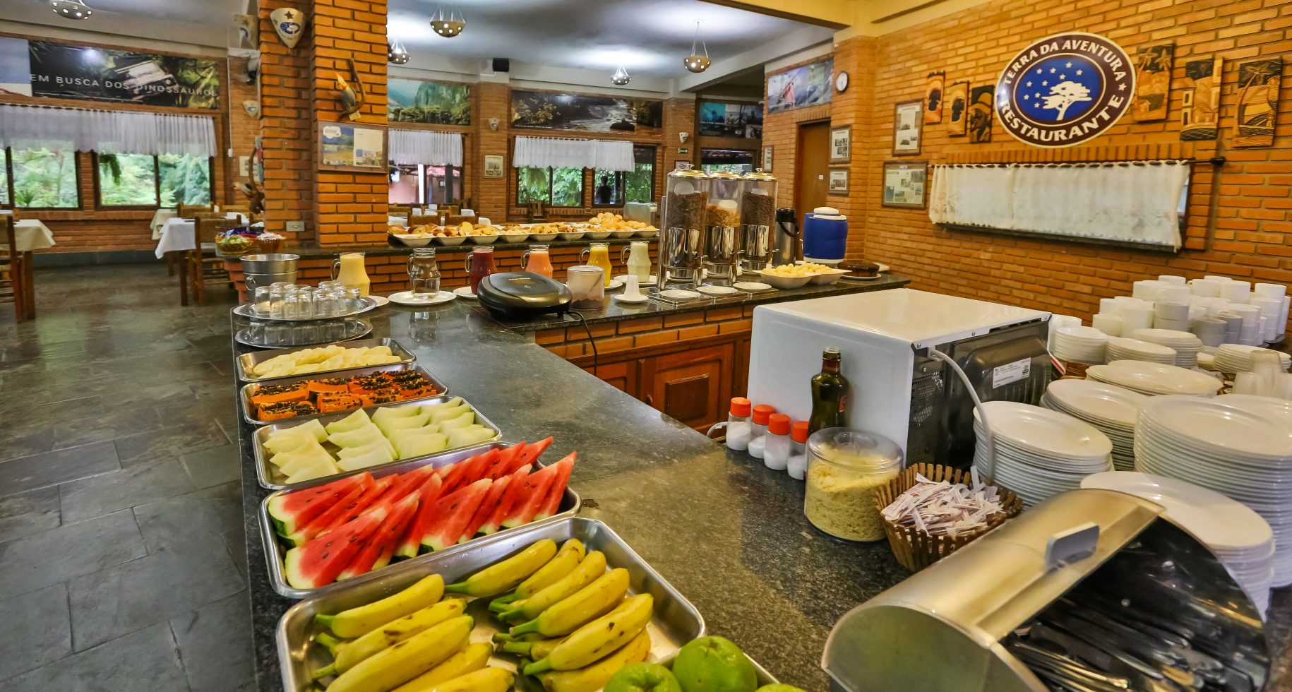 A foto mostra o restaurante do hotel fazenda parque dos sonhos com foco para a mesa de frutas e sucos, com frutas como, abacaxi, mamão, melão, melancia banana etc
