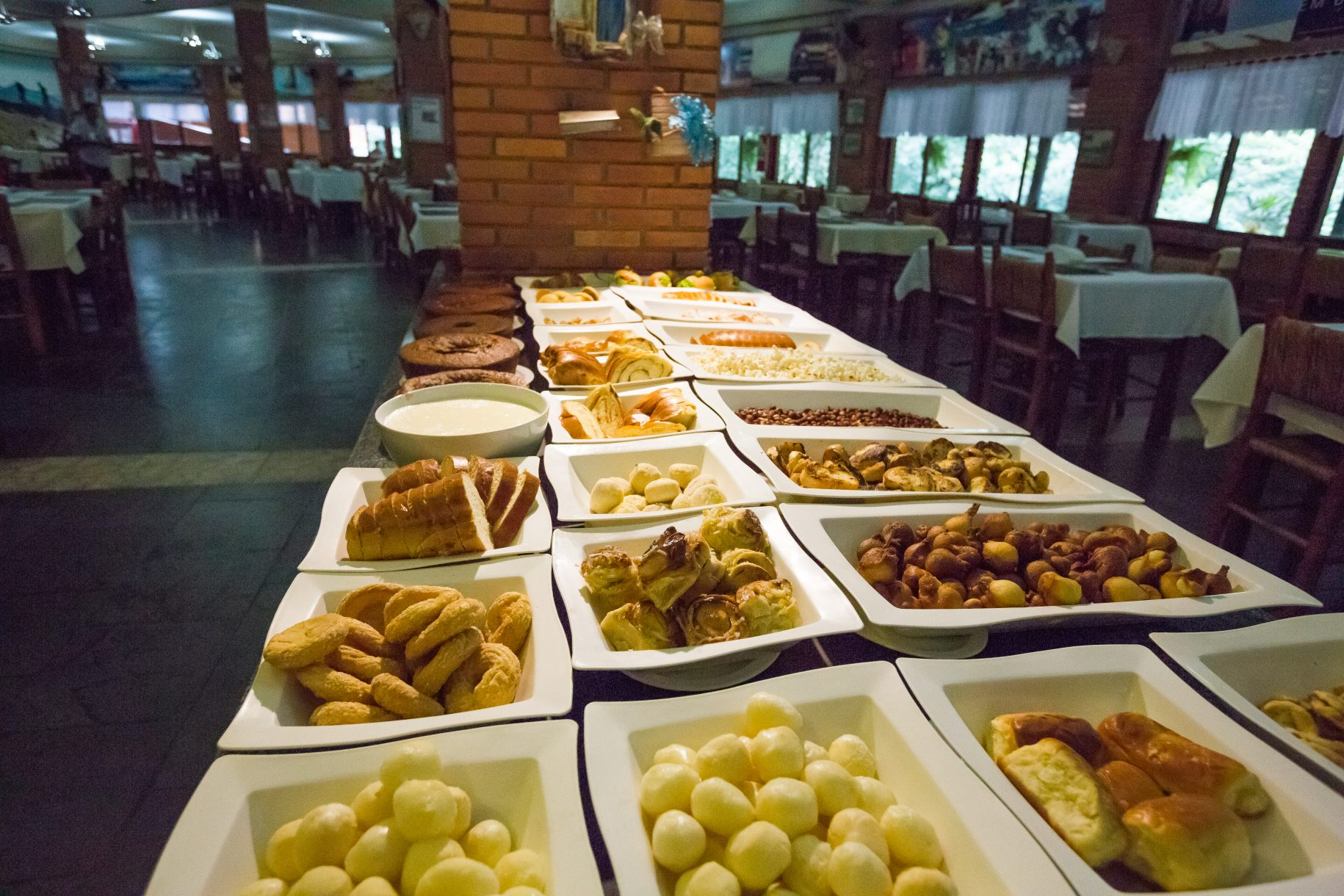 Mesa de pães e doces caseiros, no café da manhã do hotel fazenda parque dos sonhos com inúmeras opções