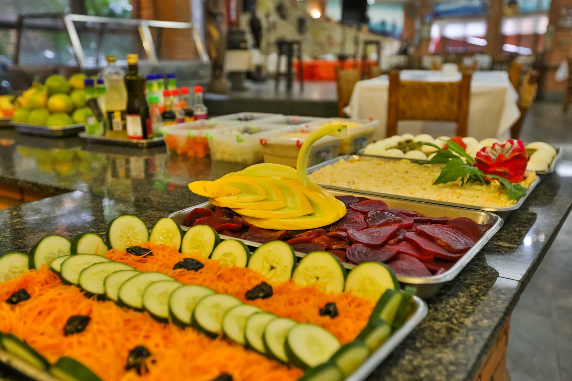 A foto mostra o restaurante do hotel fazenda parque dos sonhos com foco para a mesa de saladas no jantar