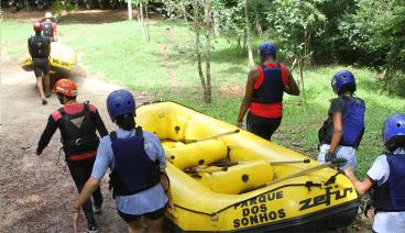 5 Pessoas carregando um bote até a água para fazer o rafting no hotel fazenda parque dos sonhos
