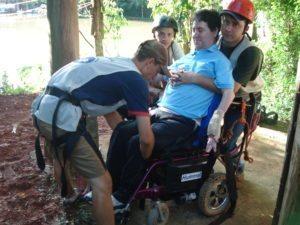 Usuário de cadeira de rodas sendo preparado para fazer a tirolesa do hotel fazenda campo dos sonhos