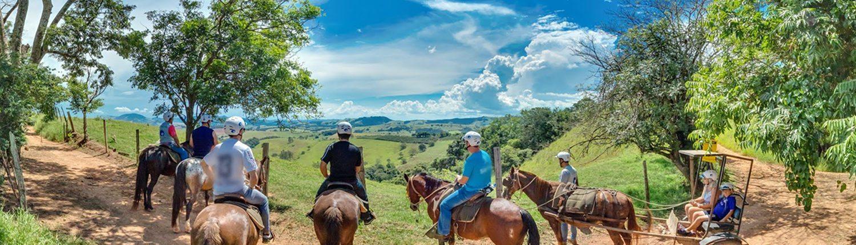 Pessoas fazendo a cavalgada das montanhas, paradas observando a linda vista das montanhas