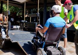 Condutores de atividade auxiliando uma pessoa usuária de cadeira de rodas a subir pela rampa na charrete, para que ele consiga fazer o passeio de charrete