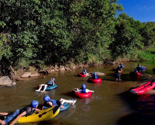 A foto mostra a atividade do boia cross sendo operada, com várias pessoas descendo o rio