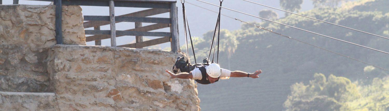 Pessoa fazendo a tirolesa voadora do hotel fazenda parque dos sonhos